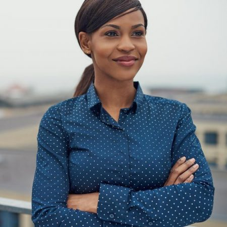 54832430 - confident friendly black business woman standing with folded arms on the rooftop of an urban commercial building smiling as she looks to the side of the camera