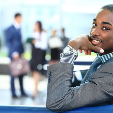 22145736 - portrait of smiling african american business man with executives working in background